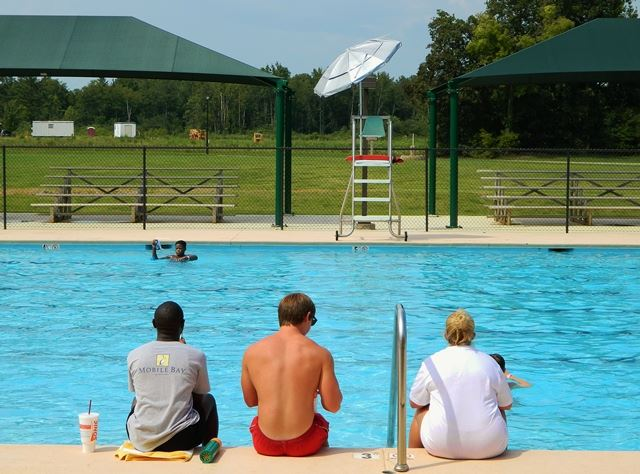 Municipal Swimming Pool with three people sitting on pool ledge
